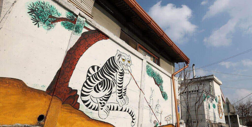 """Exemple de peinture minhwa """"tigre"""" visible sur un mur de quartier."""