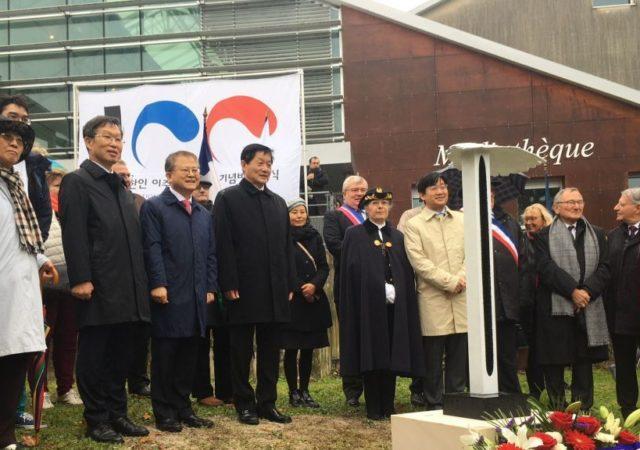Les officiels posant derrière le monument de commémoration à l'occasion du centenaire de la migration coréenne en France