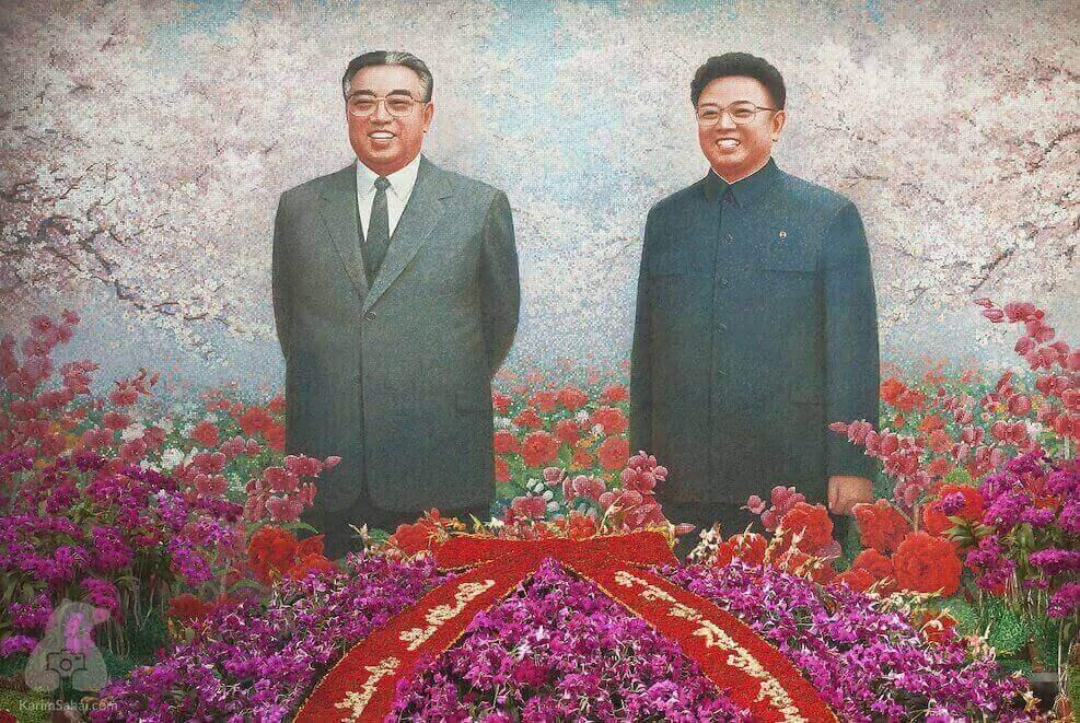 Portrait de Kim Il Sung et Kim Jong Il entourés de fleurs représentatives de la Corée du Nord
